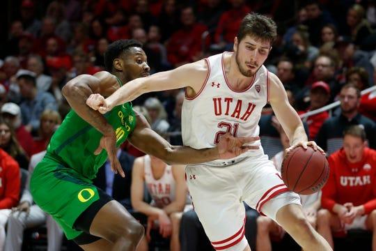 Utah forward Riley Battin (21) drives around Oregon forward Shakur Juiston (10) in the second half during an NCAA college basketball game Saturday, Jan. 4, 2020, in Salt Lake City.