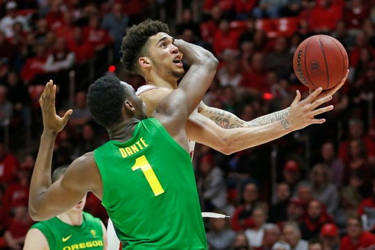Utah forward Timmy Allen, rear, is fouled by Oregon center N'Faly Dante (1) as he drives to the basket in the second half during an NCAA college basketball game Saturday, Jan. 4, 2020, in Salt Lake City.