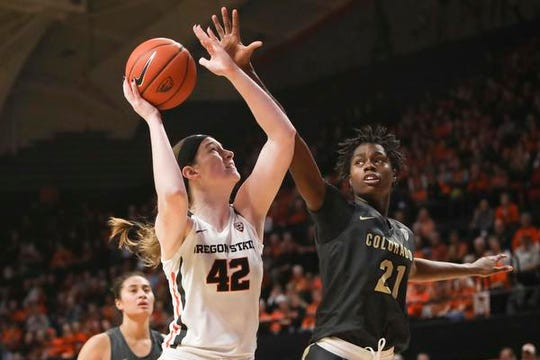 Colorado's Mya Hollingshed (21) defends against Oregon State's Kennedy Brown (42) at the basket during the second half of an NCAA college basketball game in Corvallis, Ore., Sunday, Jan. 5, 2020.  (AP Photo/Amanda Loman)