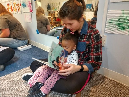 Volunteers read to children at the Budd Bell Center.