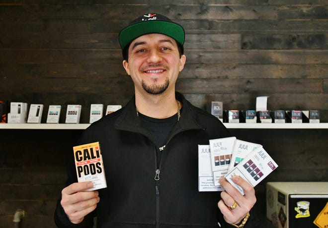 Visalia Vapes owner Josh French holds up an assortment of soon-to-be-banned Juul and pre-mixed vape pods after a recent FDA ruling outlawed most flavored vape products; a move French says he largely supports.