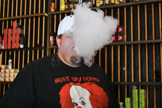 A Visalia Vapes employee takes a puff from a tank-style vape. Under a new FDA ruling, flavored e-juice that users themselves mix with nicotine to vape will remain legal.