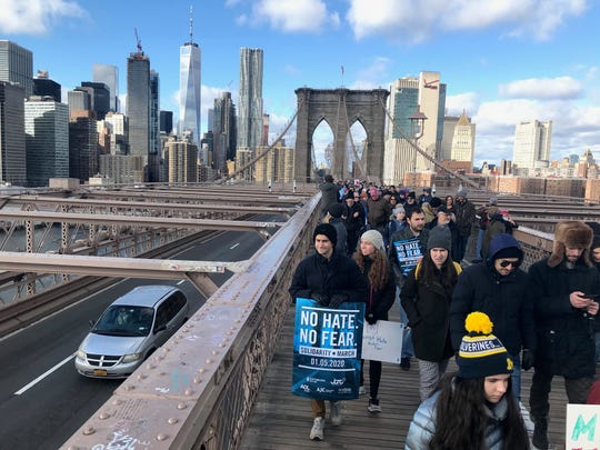 "Thousands march across the Brooklyn Bridge during the ""No Hate, No Fear Solidarity March"" in New York City on Sunday. The rally comes after the Dec. 28 stabbing attack at a Hanukkah celebration in Monsey, New York."