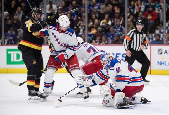 New York Rangers goalie Alexandar Georgiev (40), of Bulgaria, makes the save as Jacob Trouba (8) battles Vancouver Canucks' Antoine Roussel (26), of France, during the second period of an NHL hockey game Saturday, Jan. 4, 2020, in Vancouver, British Columbia.