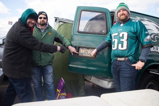 Delawareans Hugh Leahy, left, Rich Julian, center, and Stephen Julian pose for a photo with their Eagles green van and 'WNTZWGN' license plate while tailgating Sunday at Lincoln Financial Field.