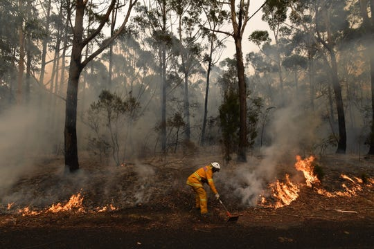 A firefighter works to contain a bushfire near Ulladulla, Australia, on Jan. 5, 2020.