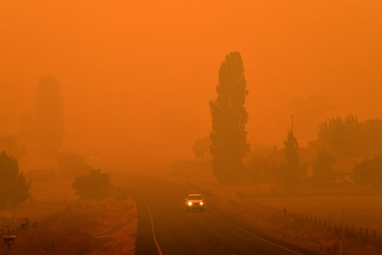 Residents commute on a road through thick smoke from bushfires in Bemboka, in Australia's New South Wales state on Jan. 5, 2020.