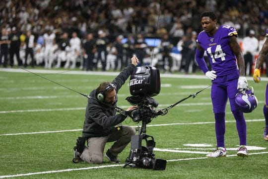 Minnesota Vikings wide receiver Stefon Diggs looks on as a technician works on an aerial television camera came down to the field during the second quarter of a NFC Wild Card playoff football game between the New Orleans Saints and the Vikings.
