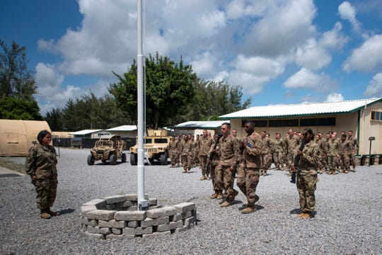 U.S. Air Force airmen from the 475th Expeditionary Air Base Squadron conduct a flag-raising ceremony, at Camp Simba, Manda Bay, Kenya in August 2019.