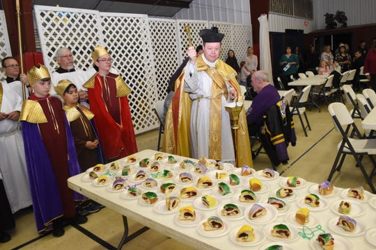 Father Chad Partain (right), pastor of St. Frances Cabrini Church, blesses the King cakes Sunday, Jan. 5, 2020. Parishioners  celebrated the Epiphany, or end of the Christmas season with a mass Sunday, Jan. 5, 2020, and ushered in the Mardi Gras season. John Gary Hines (far left), Daren Kho and Eli Aymond portrayed the Three Wise Men who presented Jesus with gifts of gold, frankincense and myrrh after following the Star of Bethlehem to find him.