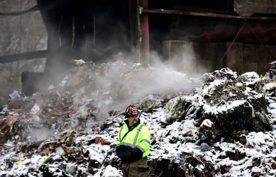 Capt. Jason Henderson of the Apalachin Fire Department looks over the scene at Taylor Garbage's recycling plant in  Apalachin on Monday morning. A fire broke out at the recycling center on Friday evening and continued to burn throughout the weekend. Monday, January 6, 2019.