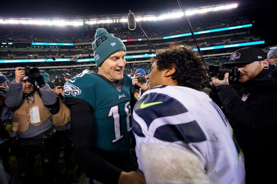 Philadelphia Eagles' Josh McCown, left, meets with Seattle Seahawks' Russell Wilson after an NFL wild-card playoff football game, Sunday, Jan. 5, 2020, in Philadelphia. Seattle won 17-9.