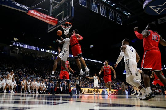 Xavier Musketeers forward Naji Marshall (13) tosses back a layup under defense from St. John's Red Storm guard Julian Champagnie (2) in the second half of the NCAA Big East game between the Xavier Musketeers and the St. John's Red Storm at the Cintas Center in Cincinnati on Sunday, Jan. 5, 2020. Xavier took a 75-67 win in the conference matchup against the Red Storm.