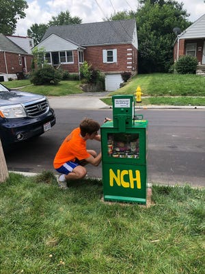 Zane Reeb installs a converted former Enquirer newspaper box painted NCH for North College Hill in July 2019. The box was reported stolen Sunday and then later returned by a man who told police he thought it was scrap.