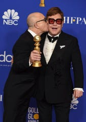 "Bernie Taupin, left, kisses Elton John in the press room with the award for best original score in a motion picture for ""I'm Gonna Love Me Again"" from 'Rocketman.'"