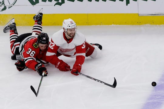 Chicago Blackhawks center Matthew Highmore, left, and Detroit Red Wings defenseman Brian Lashoff battle for the puck during the third period.