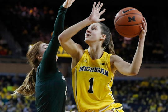 Michigan guard Amy Dilk (1) attempts a shot as Michigan State guard Taryn McCutcheon defends during the first half Sunday.