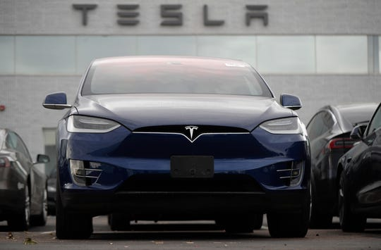 In this Oct. 20, 2019, photo an unsold 2019 Model X sits under a sign at a Tesla dealership in Littleton, Colo.