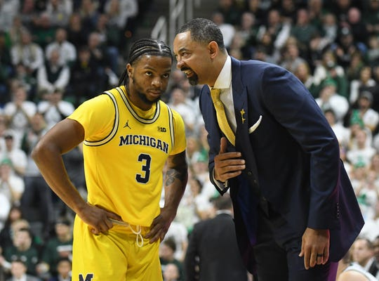 Michigan's Zavier Simpson and head coach Juwan Howard talk during a break  in the first half Saturday in East Lansing.