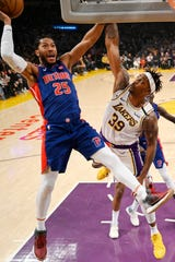 Detroit Pistons guard Derrick Rose, left, shoots as Los Angeles Lakers center Dwight Howard defends during the first half.