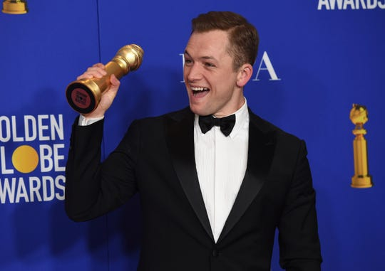 Taron Egerton poses in the press room with the award for best performance by an actor in a motion picture, musical or comedy, for 'Rocketman.'
