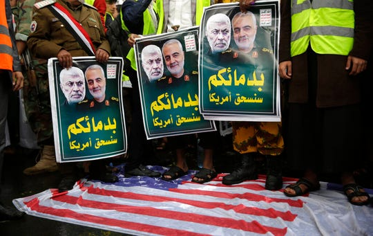 """Yemeni Shiite Houthis stand on a representation of an American flag while holding posters of Iraqi militia commander Abu Mahdi al-Muhandis, left, and Iranian military commander Qassem Soleimani during a protest against a U.S. airstrike in Iraq that killed them both, in Sanaa, Yemen, Monday, Jan. 6, 2020. Arabic writing on posters that reads, """"With your blood we will destroy America."""""""