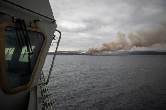 In this photo provided by the Australian Department of Defence on Jan. 6, 2020, a fire burns near Eden as HMAS Adelaide arrives to assist with wildfires. The wildfires have so far scorched an area twice the size of the U.S. state of Maryland. They have destroyed about 2,000 homes.