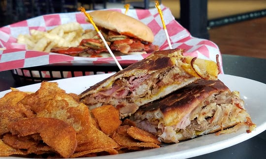 A Cuban sandwich with smoked pork, shaved ham, mustard, pickle and Swiss cheese pressed on a roll from Panaderia San Miguel at Piston's Bar and Grill.