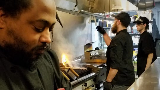 Chefs Dontae Hines and Travis Swayze and cook Sage Irons in the kitchen at The Bokeh Lounge.