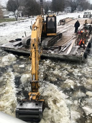A backhoe on a barge was used to help break up ice along the Oconto River in the city of Oconto over the weekend to help prevent a re-occurrence of flooding last week.