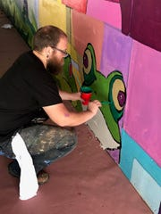 Artist David Carpenter puts some finishing touches on the 2019 Public Mural Project.