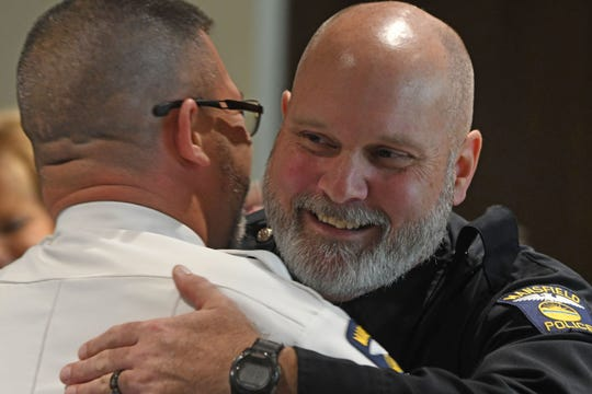 Mansfield police officer Jeffrey C. Gillis accepts congratulations from friends, family and peers Monday afternoon during his retirement party.