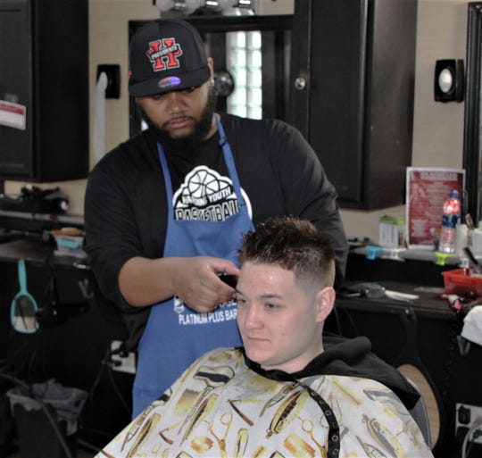 Master barber Daveon McGary finishes up cutting a customer's hair at Platinum Plus Barber Shop, 134 London Street, Marion.