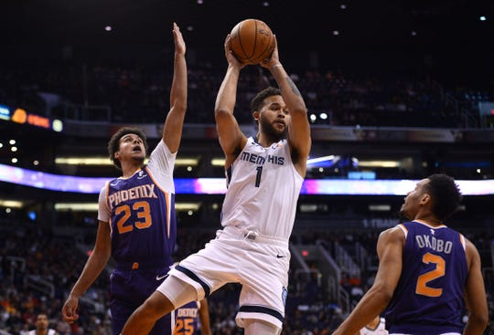 Memphis Grizzlies forward Kyle Anderson (1) passes the ball against Phoenix Suns forward Cameron Johnson (23) and forward Elie Okobo (2) during the first half at Talking Stick Resort Arena.