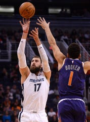 Memphis Grizzlies center Jonas Valanciunas (17) shoots over Phoenix Suns guard Devin Booker (1) during the first half at Talking Stick Resort Arena.
