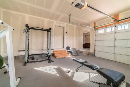 With space for larger equipment, a garage is an ideal space to set up a home gym.