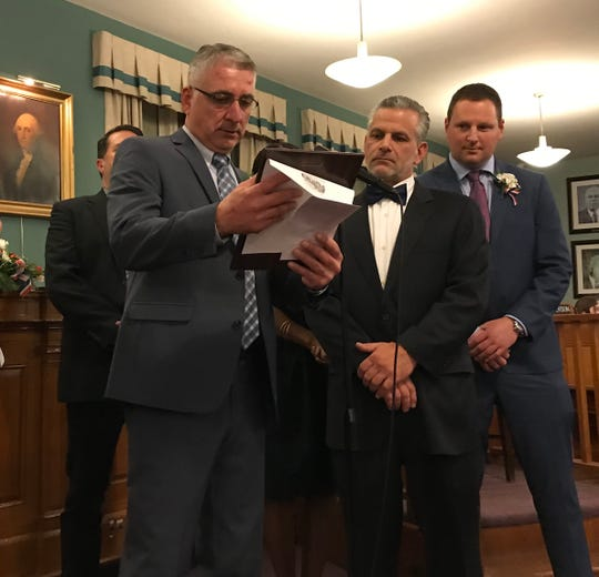 Newly minted Mayor Frank Nunziato reads a proclamation to former Mayor Joseph DeSalvo for his years of service. Council President Tom Mullahey looks on at right.