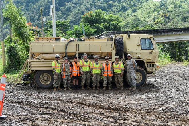 U.S. Soldiers and Airmen with the Puerto Rico National Guard pose beside a vehicle, Dec. 27, 2019 near Rio de la Plata, where Soldiers assigned to the 482nd Chemical Company and an Airmen from the 156th Medical Group extract water that is used to suppress a fire in Cayey. Airmen from the 156th Wing were activated to support state and federal operations working to stabilize the vegetation debris fire that has been burning underground in Cayey since Nov. 28, 2019.