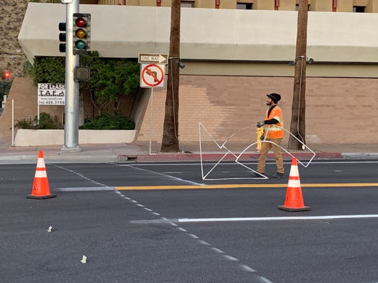 A crew member prepares to add a turn arrow on Indian Canyon Drive at Amado Road Monday, Jan. 6, 2020. Indian Canyon is being converted to a two-way street between Alejo Road and Camino Parocela and part of the southbound stretch opened to traffic Monday.