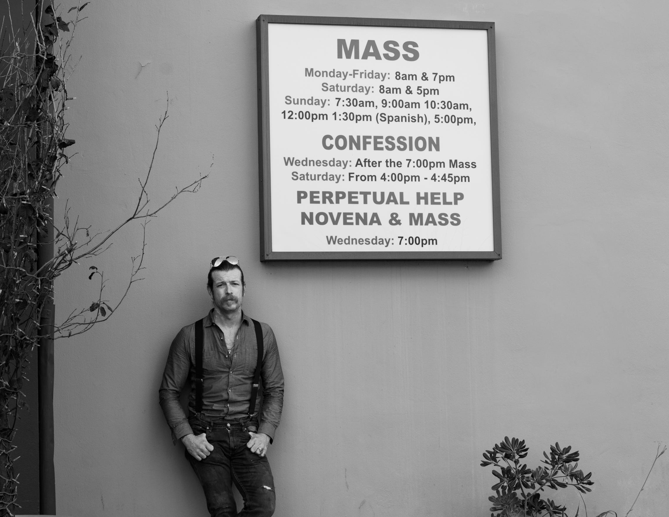 Jesse Hughes poses in front of a sign at the Holy Trinity Catholic Church in Los Angeles, Calif. on Dec. 19, 2019.