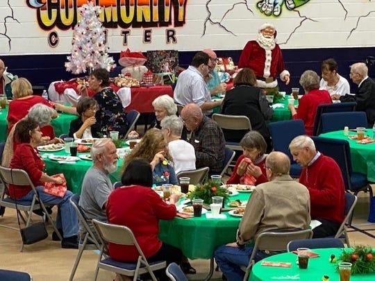 Seniors enjoy Christmas at Milton Community Center with volunteer help.