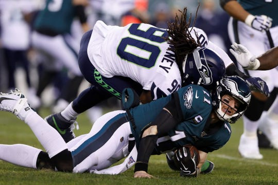 Seattle Seahawks' Jadeveon Clowney (90) hits Philadelphia Eagles' Carson Wentz (11) during the first half of an NFL wild-card playoff football game, Sunday, Jan. 5, 2020, in Philadelphia. Wentz was injured on the play. (AP Photo/Julio Cortez)
