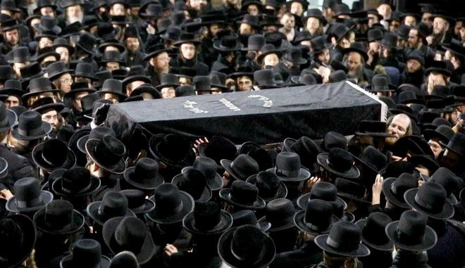 Orthodox Jewish men carry Moshe Deutsch's casket outside a Brooklyn synagogue following his funeral. Deutsch was killed Dec. 10, 2019, in a shooting inside a Jersey City kosher food market.