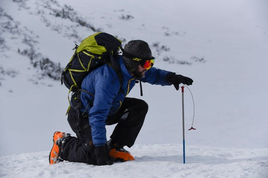Dr. Ryan Crumley measuring snow depths for the Community Snow Observations project.