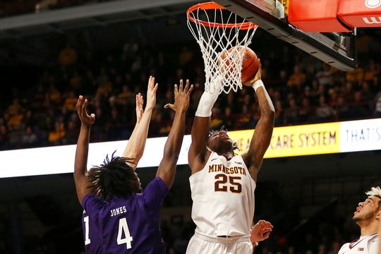 Minnesota's Daniel Oturu shoots the ball against Northwestern's Jared Jones during an NCAA college basketball game Sunday, Jan. 5, 2020, in Minneapolis.