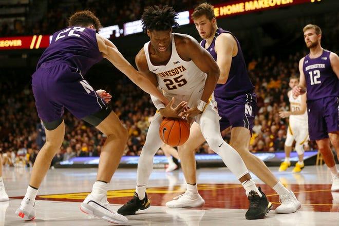 Minnesota's Daniel Oturu tries to grab a loose ball against Northwestern's Pete Nance during an NCAA college basketball game Sunday, Jan. 5, 2020, in Minneapolis. Minnesota won 77-68.