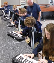 Andy Nathan assists students with the new MIDI at Holy Comforter.