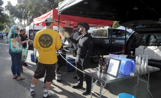 Jeremy Haffner, president and brewer of Ojai Valley Brewery, talks with shoppers at the Ventura County Certified Farmers' Market in Ventura. The brewery has started offering free samples and by-the-bottle sales of its ales and lagers at the market, which takes place from 8:30 a.m. to noon Saturdays.