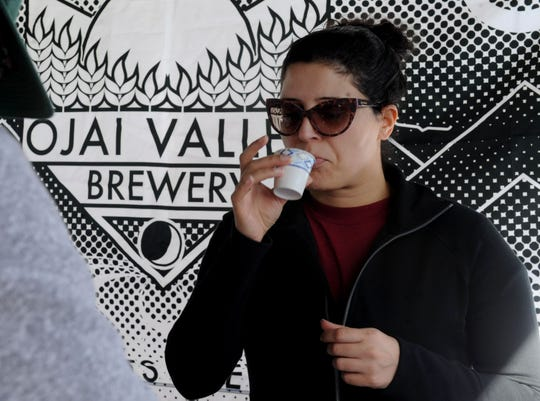 Renu Bajwa sips a sample of Ojai Valley Brewery beer at the Ventura County Certified Farmers' Market in downtown Ventura. She and her husband, Ranjeet Bajwa, went home with a bottle of Arbolada, a black lager flavored with Mexican vanilla beans.