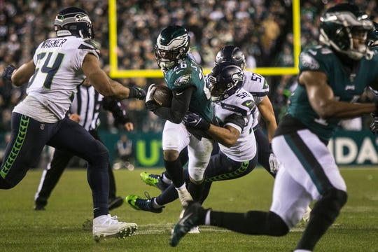 Eagles' Miles Sanders (26) is wrapped up by Seattle's K.J. Wright Sunday night at Lincoln Financial Field. The Seahawks defeated the Eagles ending their season 17-9.